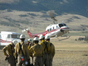 Crews on the Miner Paradise Complex wait to be shuttled to the line by helicopter. Firefighters made good progress Monday and weather looks favorable for more good work Tuesday.